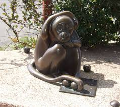 Bronze sculpture of a primate playing with balls -- but look what the balls are sitting on: it's a surreal joke.